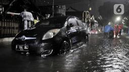 Sebuah mobil terendam saat banjir melanda kawasan Cipinang, Jakarta Timur, Minggu (23/2/2020) dini hari. Hujan deras yang mengguyur Jakarta dan sekitarnya sejak Sabtu malam ditambah buruknya drainase menyebabkan ratusan rumah di Cipinang terendam banjir. (merdeka.com/Iqbal S. Nugroho)