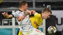 Kedua tim tampil ngotot di awal babak pertama. Borussia Dortmund membuka peluang pada menit ke-20 lewat Marco Reus (kanan). Pemain 32 tahun tersebut punya kans untuk mencetak gol setelah berhadapan satu lawan satu dengan Manuel Neuer, sayangnya gagal. (Foto: AFP/Ina Fassbender)