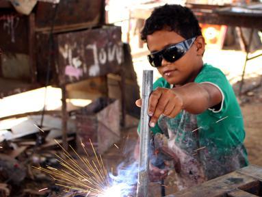 Seorang anak mengelas besi saat bekerja di distrik Abs utara di provinsi Haji Yaman, (8/5). UNICEF mengatakan hampir setengah juta anak Yaman putus sekolah sejak 2015, ketika Arab Saudi ikut campur dalam perang sipil negara itu. (AFP Photo/Essa Ahmed)