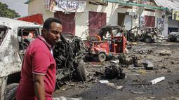 Seorang pria berjalan melewati reruntuhan di lokasi pemboman di Mogadishu, Somalia (13/2/2021). Mobil yang membawa bom itu melaju melalui pos pemeriksaan di depan Hotel Wehliye yang cukup populer di kalangan pejabat setempat dan kelompok elite Somalia. (AP Photo/Farah Abdi Warsameh)