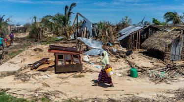 Seorang wanita melintasi rumah-rumah yang hancur akibat topan Kenneth pada bulan lalu di desa pesisir Guludo, Pulau Ibo, 13 Mei 2019. Umat Islam di Mozambik melalui bulan Ramadan dengan badai yang menyebabkan sebagian besar masjid hancur dan persediaan makanan sangat terbatas. (Zinyange Auntony/AFP)
