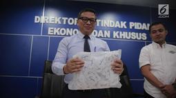 Dir Tipideksus Bareskrim Brigjen Agung Setya (kiri) menunjukkan kemasan gula rafinasi di Gedung Bareskrim, Jakarta, Rabu (1/11). Menurut pihak kepolisian, gula rafinasi tidak layak langsung dikonsumsi dan harus diolah lagi. (Liputan6.com/Faizal Fanani)