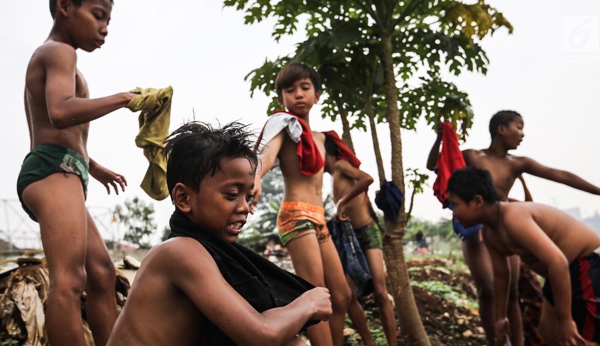 Seorang anak mencari biawak di tepi Sungai Banjir Kanal Barat, Petamburan, Jakarta, Jumat (9/11). Mendung yang menyelimuti ibukota Jakarta, tidak menyurutkan anak-anak bermain di Sungai Banjir Kanal Barat. (Liputan6.com/Fery Pradolo)