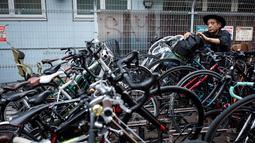 Seorang pria mengambil sepedanya dari parkiran di lingkungan Shibuya di Tokyo, Jepang (23/5/2019). Pada tahun 2008, distrik kota ini mempunyai populasi sekitar 208.371 jiwa dan kepadatan penduduk 13.337,13 orang per km². (AFP Photo/Behrouz Mehri)