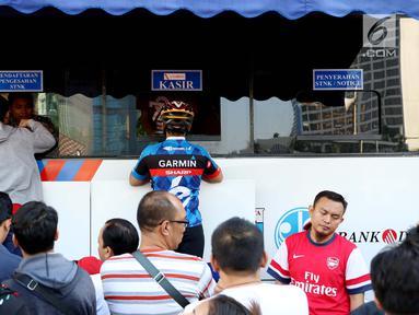 Warga membayar pajak kendaraan bermotor di samsat keliling di car free day, Jakarta, Minggu (27/8). Layanan pembayaran pajak Surat Tanda Nomor Kendaraan (STNK) bisa dilakukan tanpa membawa salinan atau BPKB. (Liputan6.com/Angga Yuniar)