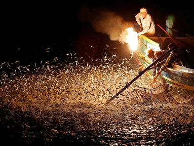 Nelayan menggunakan api sebagai umpan saat menarik ikan di perairan New Taipei City, Taiwan, (19/6). Metode tradisional ini merupakan cara nelayan taiwan untuk mendapatkan ikan tanpa menggunakan bom yang dapat merusak ekosistem laut. (REUTERS/Tyrone Siu)