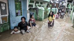 Warga menyusuri banjir yang merendam permukiman di Kebon Pala, Jakarta, Senin (8/2/2021). Banjir di Kebon Pala terus meninggi pada dini hari tadi hingga mencapai ketinggian 2,5 meter.  (merdeka.com/Iqbal S. Nugroho)