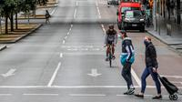 Pejalan kaki dan pesepeda terlihat di jalan kosong di Kawasan Pusat Bisnis Melbourne, Jumat (16/7/2021). Kota terbesar kedua di Australia itu kembali memberlakukan lockdown, dan kali ini selama lima hari mulai Kamis (16/7) malam karena meningkatnya klaster COVID-19. (ASANKA BRENDON RATNAYAKE/AFP)