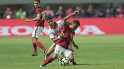 Pemain Timnas Indonesia U-23, Febri Haryadi (kanan) mencoba melewati adangan pemain Bahrain pada laga PSSI Anniversary Cup 2018 di Stadion Pakansari, Bogor, (26/4/2018). Bahrain unggul sementara 1-0. (Bola.com/Nick Hanoatubun)
