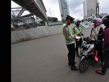 Polisi menghentikan pemotor yang ingin melintasi jalan protokol dari MH Thamrin-Medan Merdeka Barat, Jakarta, Minggu (18/1). (Liputan6.com/Miftahul Hayat)