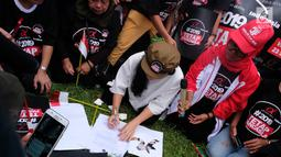 Ketua Nasional Relawan Tim Alpha Jokowi-Ma'ruf Amin, Rieke Diah Pitaloka menandatangani surat deklarasi Tim Zona Alpha Hongkong mendukung pasangan Jokowi-Ma'aruf Amin di Hongkong, Minggu (23/9). (Liputan6.com/HO/Tim Alpha)