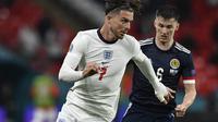 Gelandang Inggris, Jack Grealish membawa bola dari kawalan pemain Skotlandia, Kieran Tierney pada pertandingan grup D Euro 2020 di stadion Wembley, di London, Jumat (18/6/2021). Tambahan satu poin dari laga lawan Skotlandia membuat Inggris kini mengoleksi empat poin. (Justin Tallis/Pool via AP)