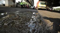 Jalan rusak dan berlubang di Jalan R.E Martadinata, Jakarta, Senin (16/2/2015). Hujan deras serta ruas jalan yang terendam air mengakibatkan badan jalan menjadi rusak dan berlubang. (Liputan6.com/Faizal Fanani)