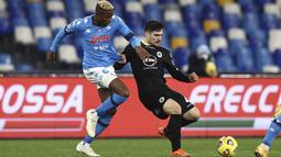 Penyerang Napoli, Victor Osimhen berusaha merebut bola dari gelandang Spezia, Gennaro Acampora pada pertandingan perempat final Coppa Italia di stadion Maradona di Naples, Italia, Jumat (29/1/2021). Napoli akan berhadapan dengan Atalanta di Semifinal.(Alessandro Garofalo/LaPresse via AP)
