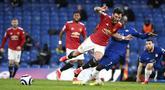 Gelandang Manchester United, Bruno Fernandes, terjatuh saat berebut bola dengan pemain Chelsea, N'Golo Kante, pada laga Liga Inggris di Stadion Stamford Bridge, Minggu (28/2/2021). Kedua tim bermain imbang 0-0. (Andy Rain/Pool via AP)
