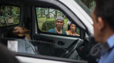 Seorang warga berkerumun melihat penemuan mayat dalam mobil di kawasan Taman Wiladatika, Jakarta Timur, Minggu (3/5/2015). Mayat pria yang diketahui bernama Sunoto (41) tersebut ditemukan oleh seorang penyapu jalanan. (Liputan6.com/Faizal Fanani)