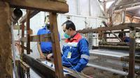 Area Manager Karaha Roy Bandoro Swandaru, tengah mencoba alat pemintal benang sutra di salah satu kelompok binaan PGE Karaha, Tasikmalaya, Jawa Barat. (Liputan6.com/Jayadi Supriadin)