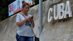 Seorang wanita menggunakan ponselnya untuk terhubung ke internet melalui WiFi di Havana, Rabu (5/12).Hampir setengah dari 11,2 juta penduduk Kuba memiliki ponsel, namun tidak semua akan mampu membeli paket internet ponsel. (YAMIL LAGE/AFP)