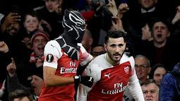 Striker Arsenal Pierre-Emerick Aubameyang (kiri) mengenakan topeng superhero Black Panther usai mencetak gol ke gawang Stade Rennes pada leg kedua babak 16 besar Liga Europa di Stadion Emirates, London, Inggris  (14/3). (Reuters/Tony O'Brien)