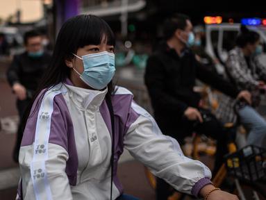 Orang-orang yang memakai masker untuk mengurangi risiko tertular virus corona COVID-19 sedang menunggu di lampu merah saat mereka bepergian dengan sepeda selama jam sibuk di Beijing, China pada 14 Oktober 2020. (Photo by NICOLAS ASFOURI / AFP)