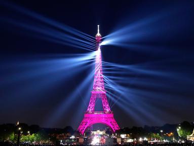Sebuah pertunjukan cahaya menyinari Menara Eiffel saat perayaan ulang tahunnya ke-130 tahun di Paris, Rabu (15/5/2019). Paris memberikan ucapan ulang tahun kepada Menara Eiffel dengan pertunjukan laser yang rumit menelusuri kembali sejarah 130 tahun monumen itu. (AP/Christophe Ena)
