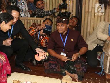 Menteri BUMN Rini Soemarno bersama Kepala Bekraf Triawan Munaf mengunjungi salah satu stand milik perusahaan BUMN selama ajang Pertemuan Tahunan IMF-World Bank Group 2018 di Nusa Dua Bali, Selasa (9/10). (Liputan6.com/Angga Yuniar)