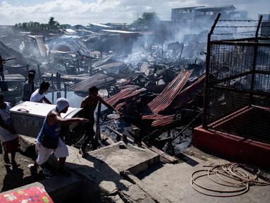 Sejumlah warga membawa barang miliknya saat rumah-rumah mereka hangus terbakar di sebuah daerah kumuh di Navotas, Manila (8/11). Dilaporkan sekitar 150 keluarga terkena dampak kebakaran tersebut. (AFP Photo/Noel Celis)