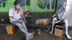 """Seorang ibu bersama sang anak yang menjadi """"Manusia Silver """" beristirahat di salah satu sudut toko di kawasan perempatan Gaplek, Pamulang, Tangerang Selatan, Sabtu (16/1/2021). Ibu tersebut mendapat penghasilan sekitar 50 ribu per hari sebagai Manusia Silver (merdeka.com/Arie Basuki)"""