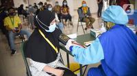 Tenaga kesehatan memeriksa tensi darah sebelum disuntik vaksin Coronavac di Rumah Sakit Darurat Covid-19 Wisma Atlet Kemayoran, Jakarta, Rabu (20/1/2021). Vaksinasi kepada 2.630 tenaga kesehatan menjadi prioritas karena bersinggungan langsung dengan pasien. (Liputan6.com/Fery Pradolo)