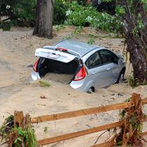 Sebuah mobil dipenuhi pasir usai tersapu banjir bandang yang melanda Ellicott City, Maryland, Amerika Serikat, Senin (28/5). (AP Photo/David McFadden)