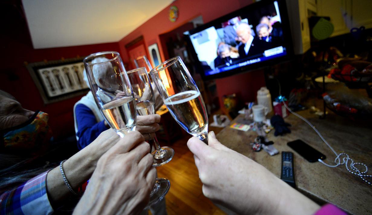 Orang-orang mengangkat gelas sampanye untuk bersulang untuk Presiden AS yang baru Joe Biden di Brattleboro, Vt, Rabu (20/2/2021). Joe Biden resmi menjabat sebagai Presiden ke-46 Amerika Serikat. (Kristopher Radder/The Brattleboro Reformer via AP)