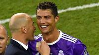 Pelatih Real Madrid, Zinedine Zidane bersama Cristiano Ronaldo melakukan selebrasi usai mengalahkan Juventus pada laga final Liga Champions di Stadion Millennium, Cardiff, Sabtu (3/06/2017). Real Madrid menang 4-1. (AFP/Ben Stansall)