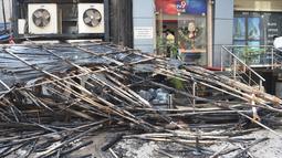 Tumpukan kayu restoran yang sebagian hangus terbakar di Mumbai, India (29/12). Restoran yang populer di India tersebut ludes terbakar dan mengakibatkan 15 orang tewas. (AFP Photo/Indranil Mukhrejee)