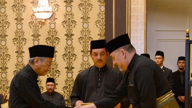 Perdana Menteri Malaysia baru, Mahathir Mohamad (kiri) bersalaman dengan Raja Malaysia Muhammad V saat prosesi sumpah jabatan di Istana Nasional di Kuala Lumpur (10/5). (AFP Photo/ Istana Nasional Malaysia)#source%3Dgooglier%2Ecom#https%3A%2F%2Fgooglier%2Ecom%2Fpage%2F%2F10000