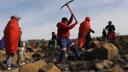 Seorang wanita menggunakan kapak saat mencari batu yang diyakini berlian di Desa KwaHlathi, luar Ladysmith, Provinsi KwaZulu-Natal, Afrika Selatan (15/6/2021). Kehebohan yang disebut-sebut sebagai 'demam berlian' ini bermula setelah penemuan batu misterius di kawasan tersebut. (AFP/Phill Magakoe)