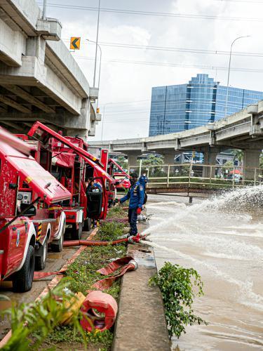 FOTO: Aksi Pemadam Kebakaran Sedot Air Banjir di Cipinang Melayu