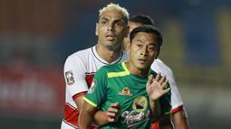 Striker Persebaya Surabaya, Samsul Arif (kanan), dijaga ketat bek Madura United, Jaimerson Xavier, dalam laga matchday ke-2 Grup C Piala Menpora 2021 di Stadion Si Jalak Harupat, Bandung, Minggu (28/3/2021). Persebaya menang 2-1 atas Madura United. (Bola.