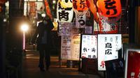 Seorang wanita yang mengenakan masker untuk mengekang penyebaran virus corona COVID-19 berjalan melewati sebuah bar di Tokyo, Jepang, Rabu (6/1/2021). Ibu kota Jepang itu mengkonfirmasi lebih dari 1.500 kasus baru virus corona COVID-19 pada 6 Januari 2021. (AP Photo/Eugene Hoshiko)
