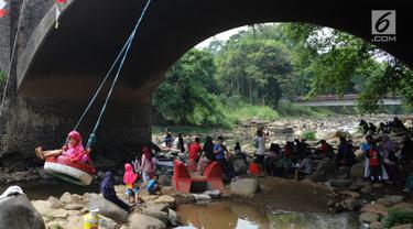 Seorang anak bermain ayunan di kolong jembatan Sempur, Bogor (16/9). Musim kemarau yang menyebabkan debit Sungai Ciliwung menyusut drastis dimanfaatkan warga Bogor dan sekitarnya untuk berwisata murah dan gratis di aliran sungai. (Merdeka.com/Arie Basuki)