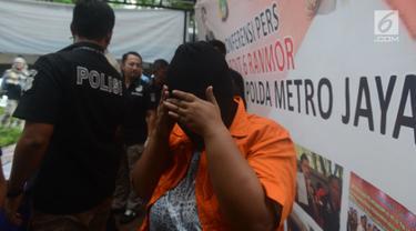 Seorang tersangka menutupi wajahnya saat dihadirkan polisi dalam rilis kasus praktik prositusi di Apartemen Kalibata City, Jakarta, Kamis (29/3). Polisi mengamankan empat tersangka, SL, IP, MP dan YP bersama barang bukti. (Merdeka.com/Imam Buhori)