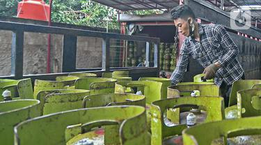 Pekerja menata tabung LPG 3 kg di agen LPG kawasan Cibubur, Jakarta, Jumat (26/2/2021). Pemerintah berencana mengalokasikan dana subsidi LPG 3 kg pada tahun 2021 sebesar Rp 37,85 triliun. (Liputan6.com/Herman Zakharia)