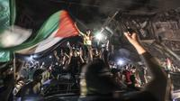 Warga mengibarkan bendera Palestina saat merayakan gencatan senjata antara Israel dengan Hamas di depan bangunan yang hancur di Kota Gaza, Palestina, Jumat (21/5/2021). Israel melakukan gencatan senjata dengan gerakan Islam yang berkuasa di Jalur Gaza, Hamas. (MAHMUD HAMS/AFP)