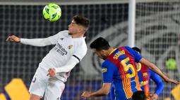 Gelandang Real Madrid, Federico Valverde (kiri) berduel udara dengan gelandang Barcelona, Sergio Busquets dalam laga lanjutan Liga Spanyol 2020/2021 pekan ke-30 di Alfredo di Stefano Stadium, Madrid, Sabtu (10/4/2021). Real Madrid menang 2-1 atas Barcelona. (AFP/Javier Soriano)