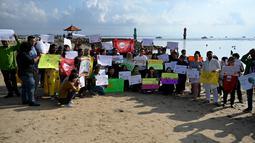 Massa mengangkat plakat saat kampanye perubahan iklim global di Pantai Sanur, Bali, Jumat (20/9/2019). Kampanye ini menuntut tindakan yang lebih cepat untuk mengatasi perubahan iklim global. (SONNY TUMBELAKA/AFP)