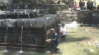 33 perawan di Desa Seloliman, Kecamatan Trawas, Kabupaten Mojokerto, Jawa Timur bejalan kaki sejauh tiga kilometer menuju situs petirtaan Jolotundo, di tangan masing-masing menggenggam erat kendi berisi air suci. (Liputan6.com/Dian Kurniawan)