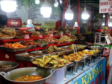 Warga memilih menu makanan khas Sumatera Barat yang dijajakan di kawasan Food Street Kramat, Jakarta, Jumat (30/4/2021). Kawasan yang menjual beragam menu makanan khas Sumatera Barat selalu ramai dikunjungi pecinta kuliner terutama jelang waktu berbuka puasa. (Liputan6.com/Helmi Fithriansyah)