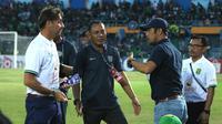 Pelatih Persebaya Surabaya, Wolfgang Pikal (kiri), tampak terlibat sebuah perdebatan dengan pelatih Persela Lamongan, Nilmaizar (menggunakan topi), usai pertandingan antara kedua tim yang berakhir 1-0 untuk kemenangan Persela, Rabu (23/10/2019). (Bola.com/Aditya Wany)