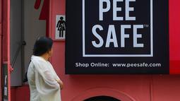 Foto pada 9 Februari 2020 menunjukkan seorang perempuan  berjalan melewati toilet keliling di sebuah bus di taman umum di Pune, India. Proyek Ti Toilet, sebuah bus yang diubah menjadi toilet dan diluncurkan pada tahun 2016, adalah gagasan Ulka Sadalkar dan Rajeev Kheer. (Indranil MUKHERJEE/AFP)
