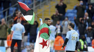 Gelandang Manchester City, Riyad Mahrez mengibarkan bendera Palestina saat merayakan timnya meraih gelar Liga Inggris usai mengalahkan Everton di stadion Etihad di Manchester, Minggu (23/5/2021). City menang besar atas Everton dengan skor 5-0. (AP Photo / Dave Thompson, Pool)