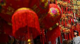 Seorang wanita melihat-lihat dekorasi Tahun Baru Imlek atau perayaan Tet di sebuah pasar pusat Kota Tua Hanoi, Senin (28/1). Di Vietnam, tahun baru imlek dikenal dengan nama Tet Nguyen Dan atau lebih akrab disingkat sebagai Tet. (Manan VATSYAYANA/AFP)